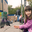 Small caucasigirl feeding pigeons — Stockfoto #35038785