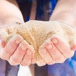 Hands holding sand — Stock Photo