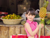 Little girl at fruits — Stock Photo