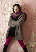 Beautiful woman with pink stockings standing in front of an old pink wall — Stock Photo