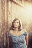 Hermosa mujer de pie en la pared de madera — Foto de Stock