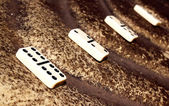 Four White Dominoes On Sloping Textured Surface — Stock Photo