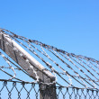 Coiled Razor Wire Fence Against Blue Skyline — Stock Photo #37699817