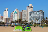 Tents Pitched 0n Beach Against City Skyline — Stock Photo