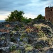 Stock Photo: Abandoned ruin of stronghold on peak of basalt mountain in night. Blur clouds on sky.