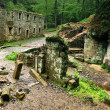 Ruin of old water abandoned mill house, stony walls, windows, empty dry millrace. — Stock Photo #28907069