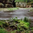 View over dark mountain river with high water level after heavy rains to ruin of stony water mill. — Foto Stock