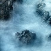 Sharp reef in blue troubled water, salt spray above, noisy waves. — Stock Photo