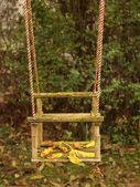 Abandoned baby swing, autumn leaves. — Stock Photo