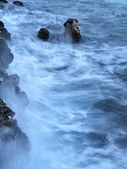 Rocks in blue troubled watter. — Stock Photo