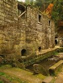 Ruin of old water abandoned mill house, stony walls, windows, empty dry millrace. — Stock Photo