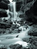 Night winter view to icicles and icy boulders into the stream. — Stock Photo