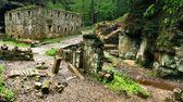 Ruin of old water abandoned mill house, stony walls, windows, empty dry millrace. — Stock Photo