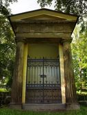 Old village chapel in the park at old graveyard in shadows of old alder trees and lindens. Rusty forged gate is closed. — Stock Photo