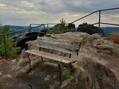 Summer evening before storm on peak path in Saxon Switzerland, grey sky over sandstone rocks. Wooden bench on main view point. — Stockfoto