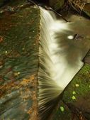 Small weir on mountain stream, water is running over basalt boulders. — Stock Photo