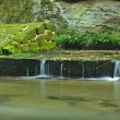 Ruins of sandstone weir on small mountain river. Stream is flowing over sandstone blocks and makes milky water. — Stock Photo