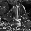 Water spray below small waterfall on mountain stream, water is falling over mossy sandstone boulder. The spray create on level and gravel milky water. — Stock Photo