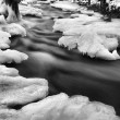 Night winter view to frozen brook, icy twigs and icy boulders above rapid stream. Reflections of light in icicles. Black and white photo. Extreme freeze.  — Stock Photo