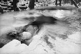 夜の冬は凍った小川、氷のような小枝および急速なストリーム上の氷のような岩を表示します。つららの光の反射。黒と白の写真。極端な凍結. — ストック写真
