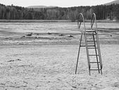 Abandoned beach at empty pond with old blue kids slide above muddy place and dirty beach sand. Autumn melancholic atmosphere. — Stock Photo