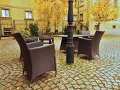 Chairs and table in garden at pedestrian precinct, yellow birch leaves on the granite pavement. — Stock Photo