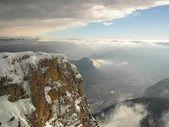 スキー場の山のピークは低い霧からはみ出しています。. — ストック写真