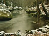 Big sandstone boulders on river bank and in clear water of stream. Winter is beginning at mountain river. — Stock Photo