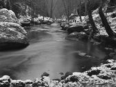 Dark cold water of mountain stream in winter time between big boulders with snowflakes of first powder snow. — Stock Photo
