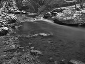 Big boulders in clear water of stream. Winter is beginning at mountain river. — Stock Photo