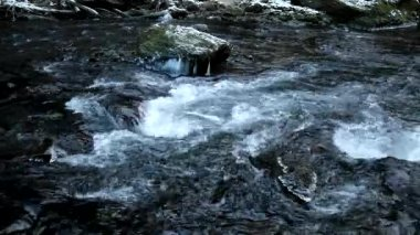 Dark cold water of mountain stream in winter time between big boulders with snowflakes of first powder snow. — Stock Video
