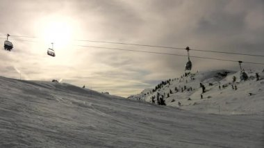 Running rope way above fresh powder snow on slope in ski resort . Evening sun in cloudy sky. — Stock Video