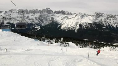 View from cable-way down to downhill skiing and snow boarding on a snowy slope in Alps ski resort. — Stock Video