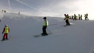 Peak of mountain with slope for downhill skiing in Alps ski resort, bunch of skiers from ski school enjoying fresh powder snow on slope. Sunny winter day in Alps. — Stock Video