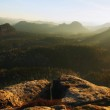 Cold spring sunrise between sandstone peaks increased from gentle mist, bright trails of sun rays in mist. — Stock Photo #41959143