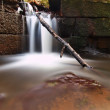 Small waterfall on small mountain stream, mossy sandstone block and water is jumping down into small pool — Foto Stock