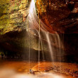 Small waterfall on small mountain stream, mossy sandstone block and water is jumping down into small pool. Water streams with sun rays, orange sand with sediments below. — Stok fotoğraf #42402975