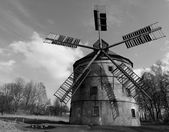 Renewal wind mill house into summer house. New red roof, repaired wind blades. Black and white photo. — Stock Photo