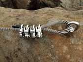 Iron twisted rope fixed in block by screws snaphooks. Detail of rope end anchored into sandstone rock. — Stock Photo