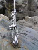 Iron twisted rope fixed in block by screws snaphooks. Detail of rope end anchored into sandstone rock — Stock Photo