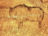 Abstract children art in sandstone cave. Black carbon paint of bison on sandstone wall, copy of prehistoric picture. — Stock Photo