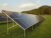 Industrial landscape with photovoltaic power plant on meadow with green grass. — Stock Photo