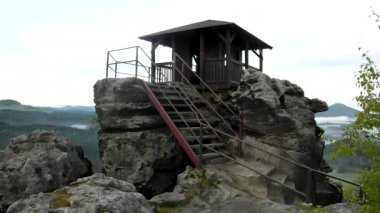 Wooden cabin on main peak of rock as view point, dark clouds in the sky. Summer early morning in sandstone rocks. — Stock Video