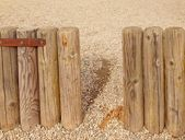 Broken old wooden palisade, old wooden stockade, fence, stony background. — Stock Photo