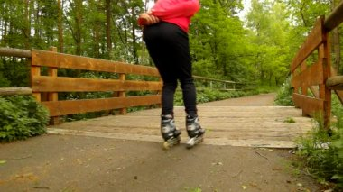 A closeup view to man in pink and black sportswear with black red white rollerblades The man is quickly blading on asphalt way in park, grass and leaves on the ground — Stock Video