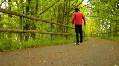 Una vista de cerca al hombre en ropa deportiva rosa y negro en la carretera. el hombre está corriendo rápidamente por camino de asfalto en el parque, pasto y hojas en el suelo. — Vídeo de stock