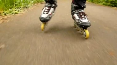 A closeup view to legs in sportswear with black red white rollerblades. The man is quickly blading on asphalt way in park, grass and leaves on the ground. — Stock Video