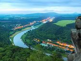 Early spring morning above big river after rainy night, fresh blue cloud in the sky, lights in town on river banks. Spring green forests in landscape, daybreak at horizon. — Stock Photo