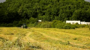 Big tractor is turning and harvesting grass. Tractor with hay maker working on the meadow in farmland. Haymaking in the countryside below hills. Summer windy evening. — Stock Video