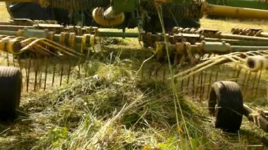Big harvesting machine is turning above dry grass, truck with hay maker working on the meadow in farmland. Haymaking in the countryside. Hot summer day. — Stock Video